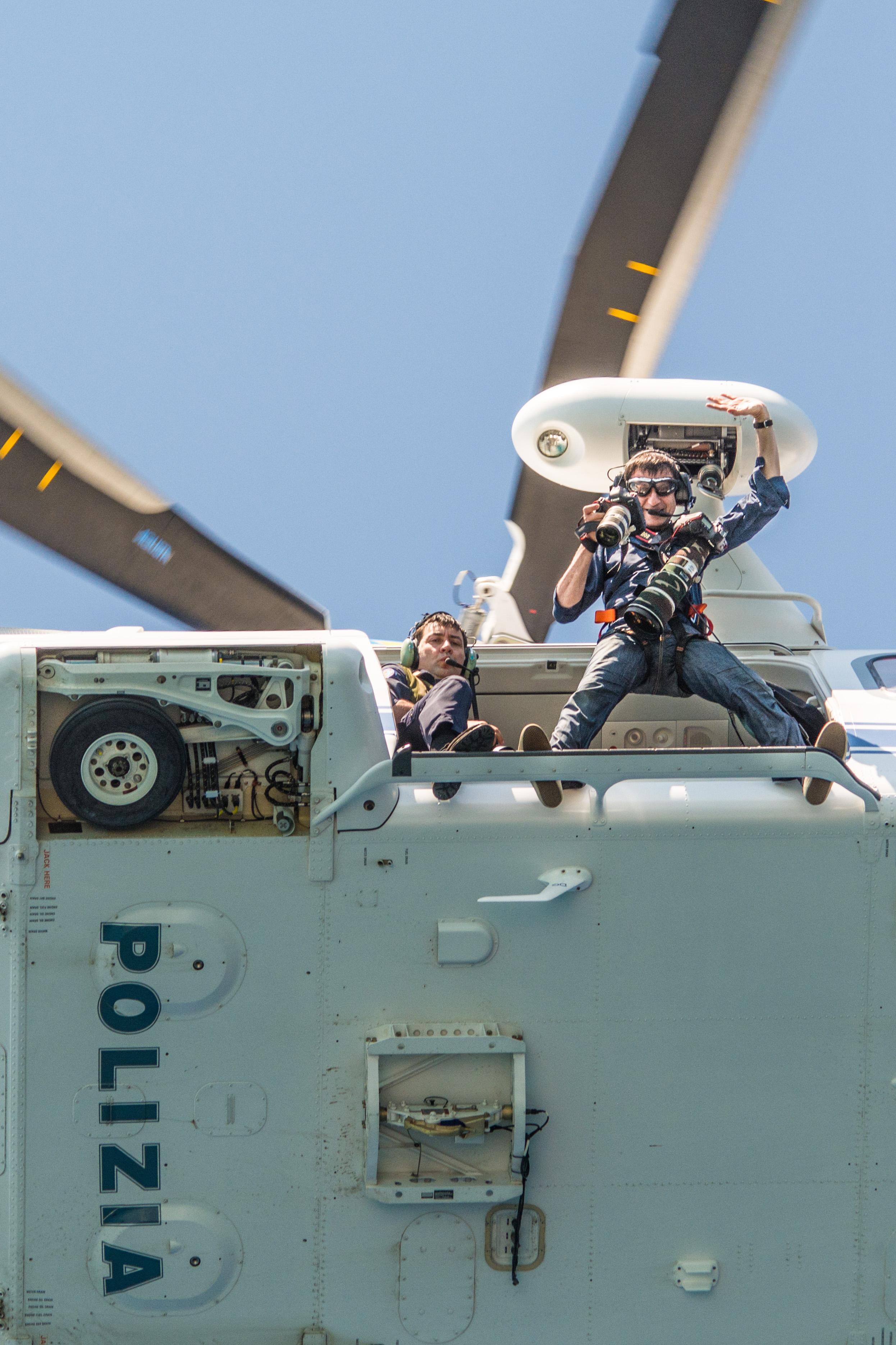 Tavolara (OL), Massimo Sestini fotoreporter imbracato fuori dall'elicottero della Polizia di Stato mentre realizza il calendario zenit 2016 2015-06-22 © Massimo Sestini