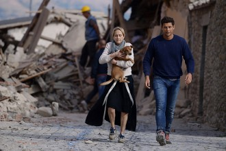 TOPSHOT - A woman holds a dog in her arms as she walks with a man next to the rubble of buildings in Amatrice on August 24, 2016 after a powerful earthquake rocked central Italy.   The earthquake left 38 people dead and the total is likely to rise, the country's civil protection unit said in the first official death toll. Scores of buildings were reduced to dusty piles of masonry in communities close to the epicentre of the pre-dawn quake in a remote area straddling the regions of Umbria, Marche and Lazio. / AFP / FILIPPO MONTEFORTE        (Photo credit should read FILIPPO MONTEFORTE/AFP/Getty Images)