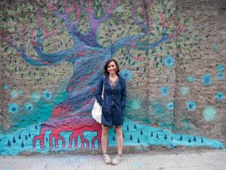 L'artista siriana Diala Brisly di fronte al suo murale in via XXIV maggio - messina
