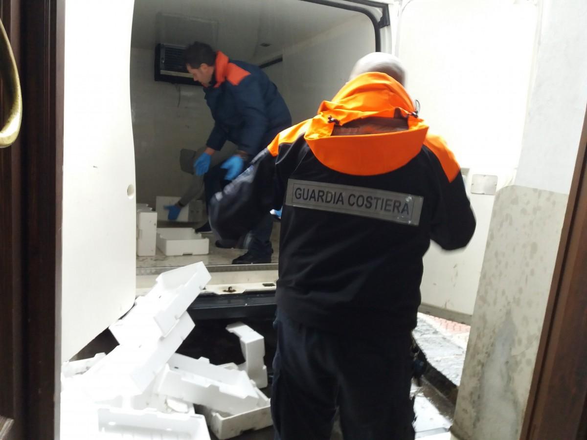 Foto che ritrae gli agenti della guardia costiera mentre sequestrano le casse di novellame