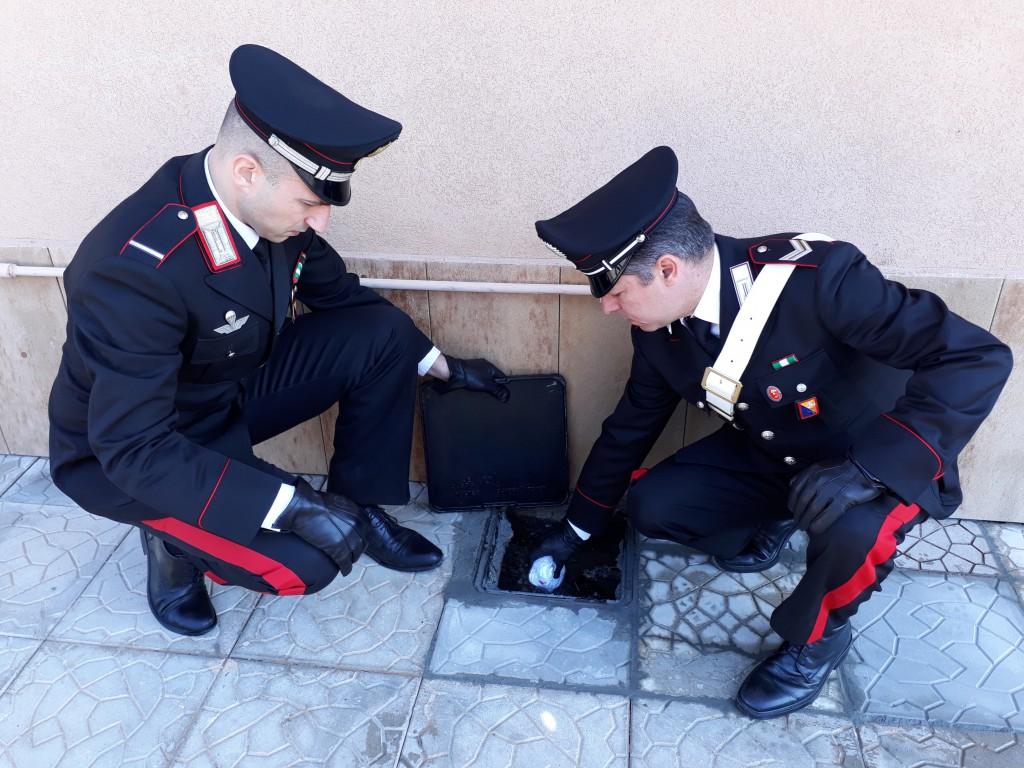 Foto di due militari dell'Arma che recuperano della cocaina gettata in uno scarico