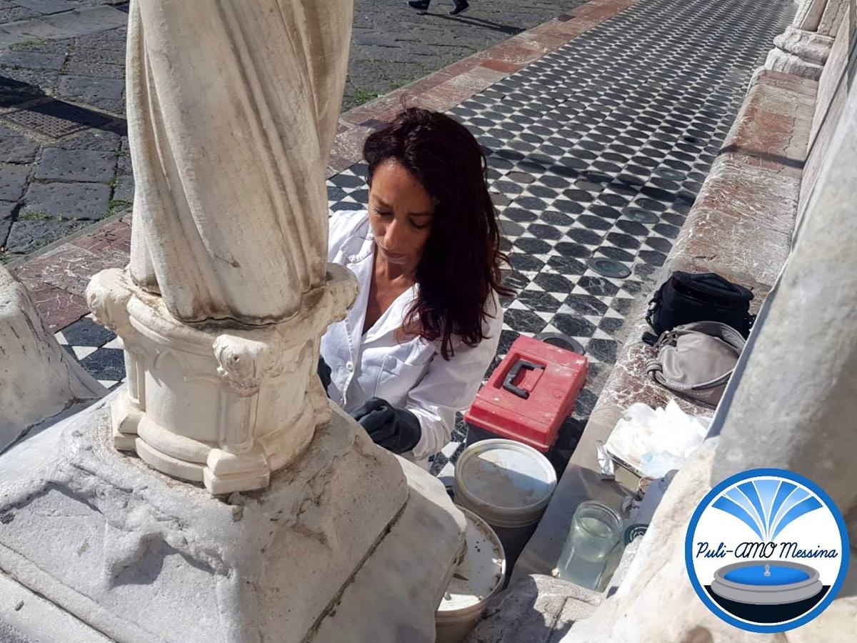 la restauratrice fedra sciacca mentre pulisce le colonne del duomo imbrattate da una scritta con pennarello nero indelebile