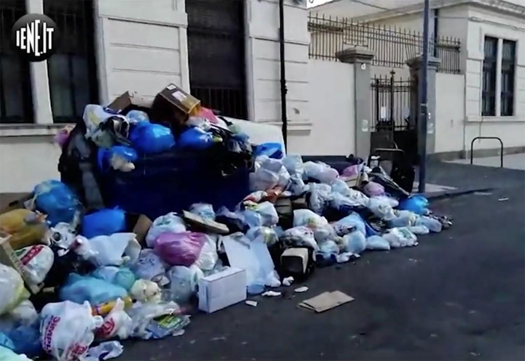 foto dei cassonetti colmi di immondizia e dei sacchetti gettati in strada di fronte alla scuola elementare cesare battisti di Messina in un servizio de Le ieie