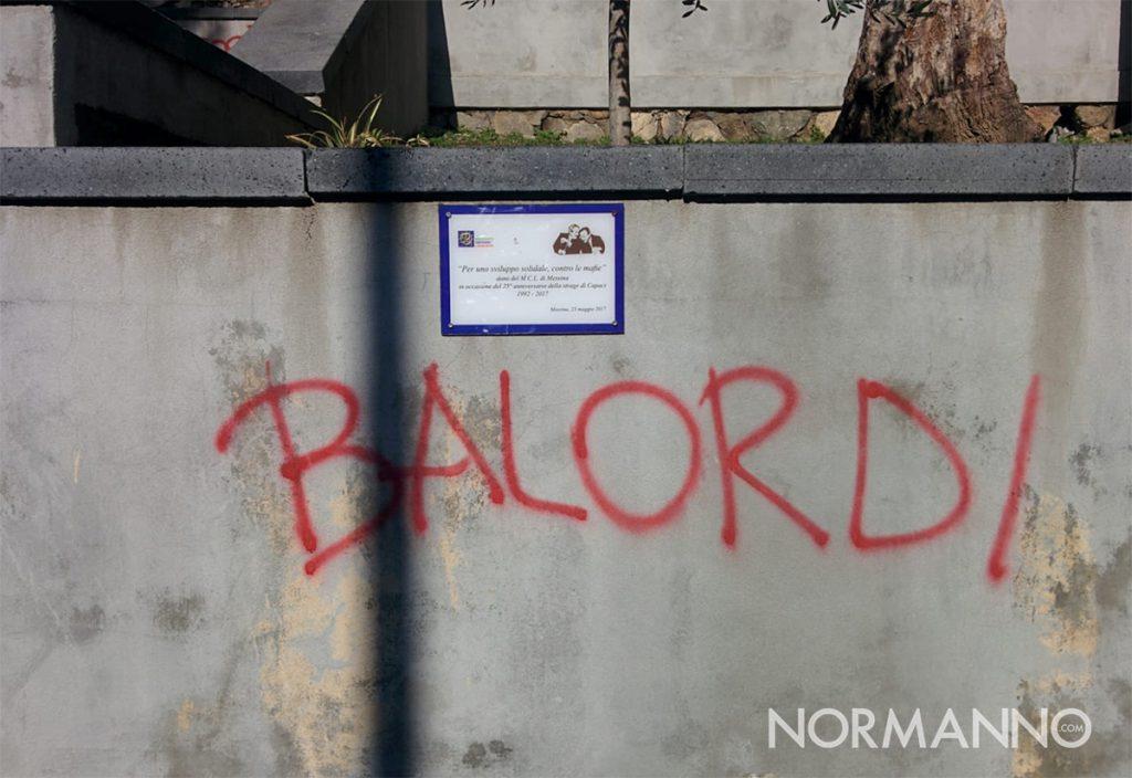 scritta che imbratta il muro su cui è apposta la targa in memoria di Falcone e Borsellino
