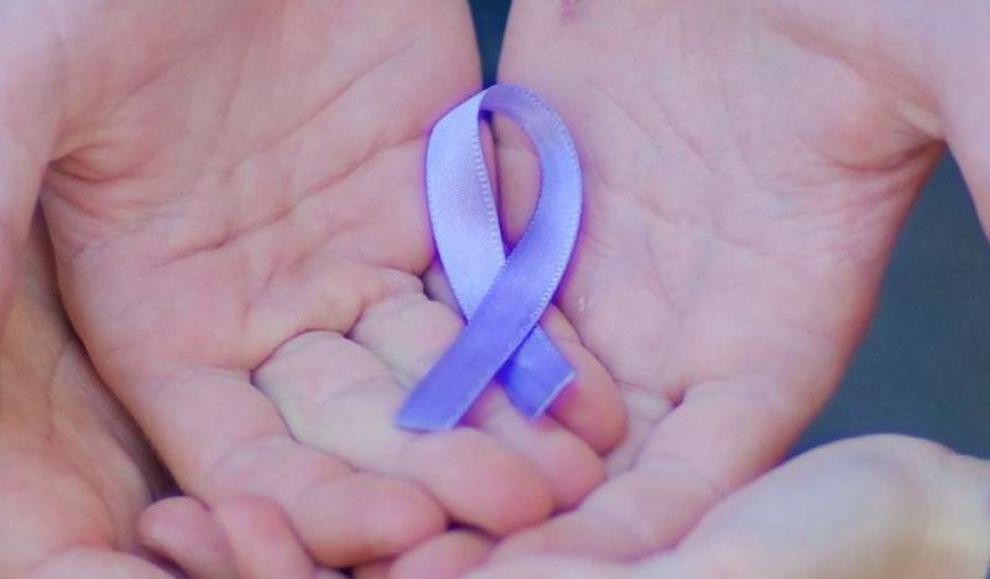 Mani che tengono un fiocchetto lilla, simbolo della giornata sui disturbi alimentari