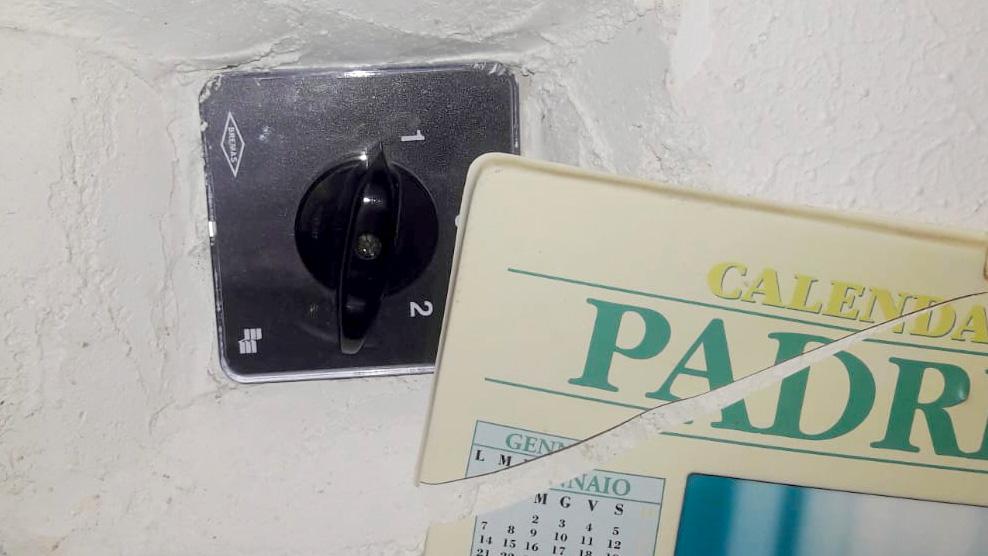 foto del dispositivo usato per un allaccio abusivo alla rete elettrica di messina nascosto da un calendario di padre pio