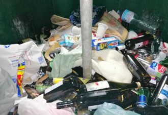 sacchetti pieni di bottiglie abbandonati accanto ai contenitori del vetro colmi di plastica e carta