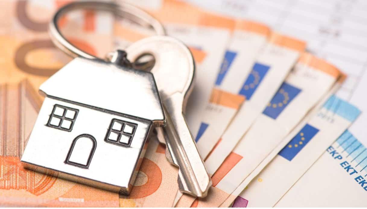 immagine di repertorio di una casa e dei soldi, indica il bonus affitto o sgravi sul pagamento della casa