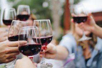 foto di persone che brindano con bicchieri di vino rosso
