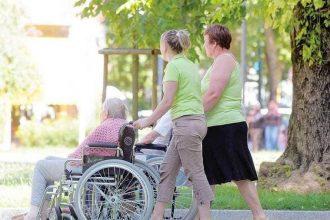 foto di un'anziana sulla sedia a rotelle con la badante