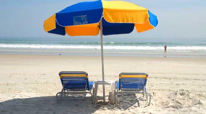 foto di due sdraio e un ombrellone in spiaggia, in riva al mare