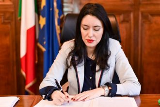 foto del ministro dell'istruzione Lucia Azzolina alla scrivania che firma delle carte