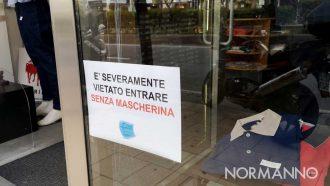 """cartello """"vietato entrare senza la mascherina"""" in un negozio di messina durante la riapertura post lockdown da coronavirus"""