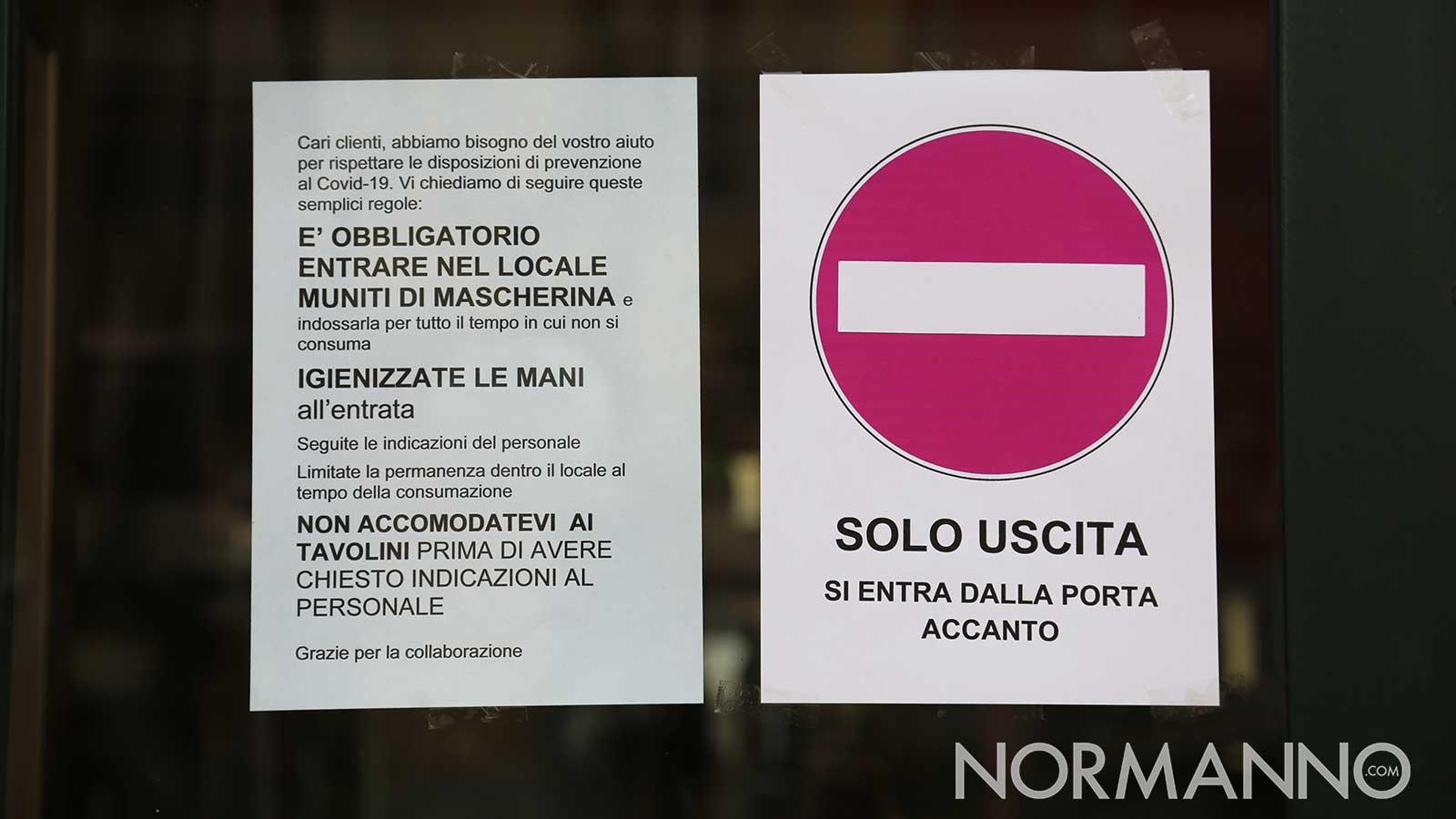cartelli esposti sulla vetrina di un bar durante la fase 2 del coronavirus