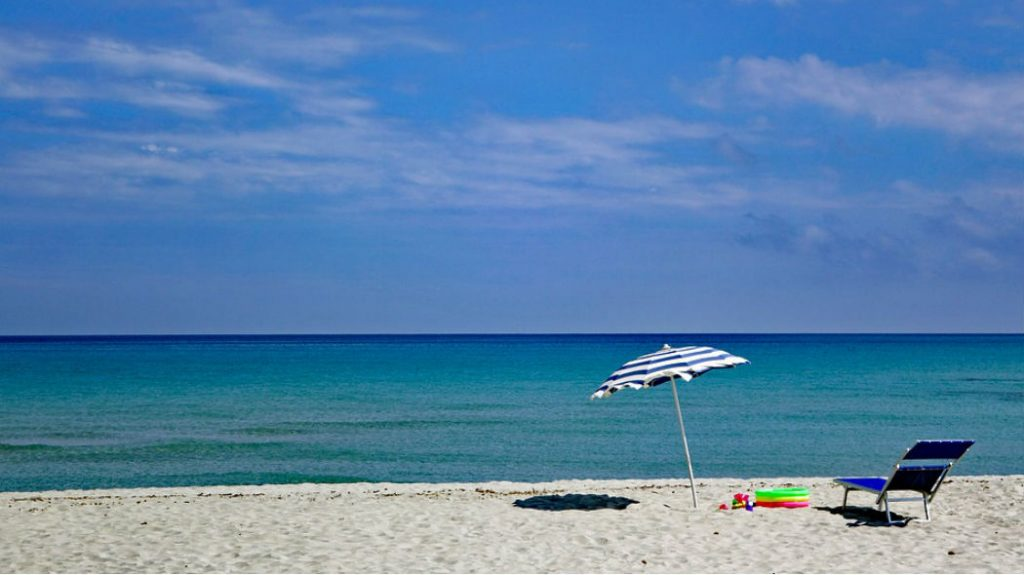 foto di una spiaggia con sdraio e ombrellone
