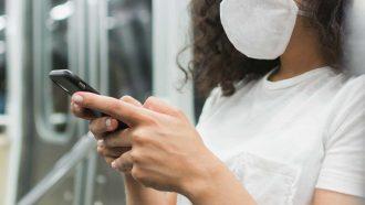 donna al cellulare con la mascherina