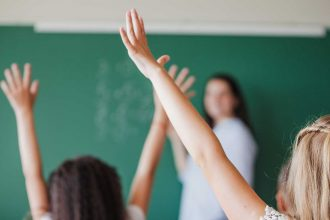 bambini che alzano la mano a scuola