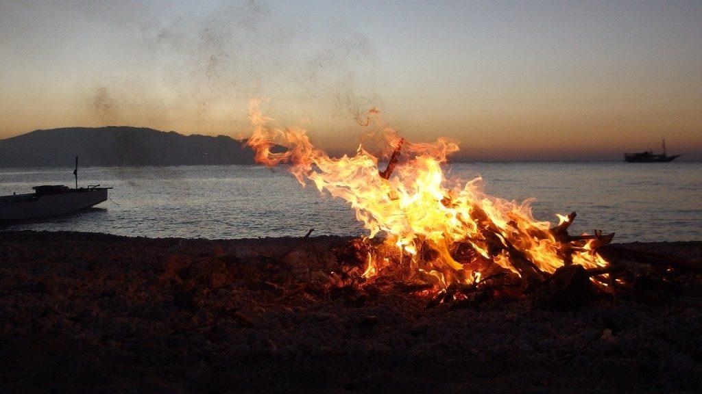 foto di un falò di sera sulla spiaggia