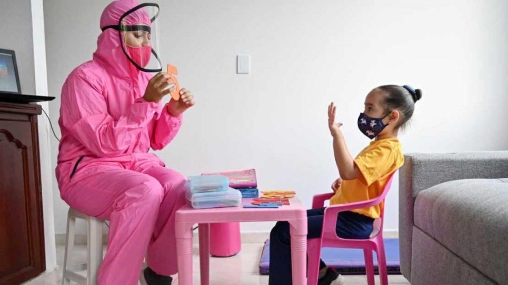 un'insegnante in tuta anti-coronavirus fa lezione a casa a una bambina