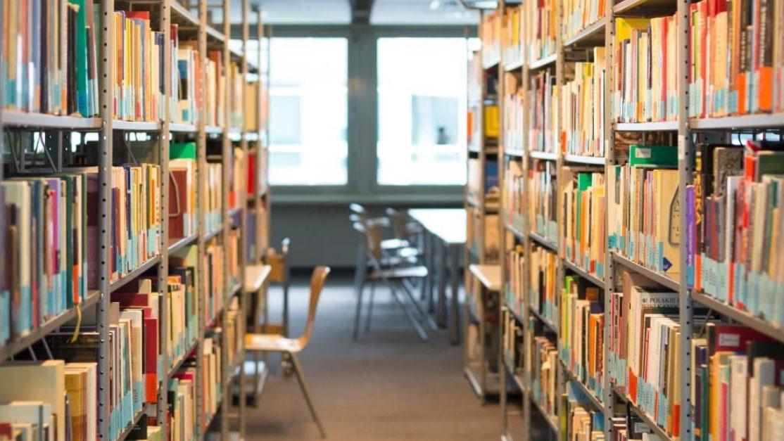 foto del corridoio di una biblioteca con gli scaffali pieni di libri