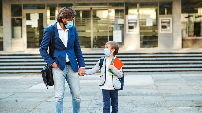 foto di un uomo e un bambino di fronte alla scuola con le mascherine per il coronavirus