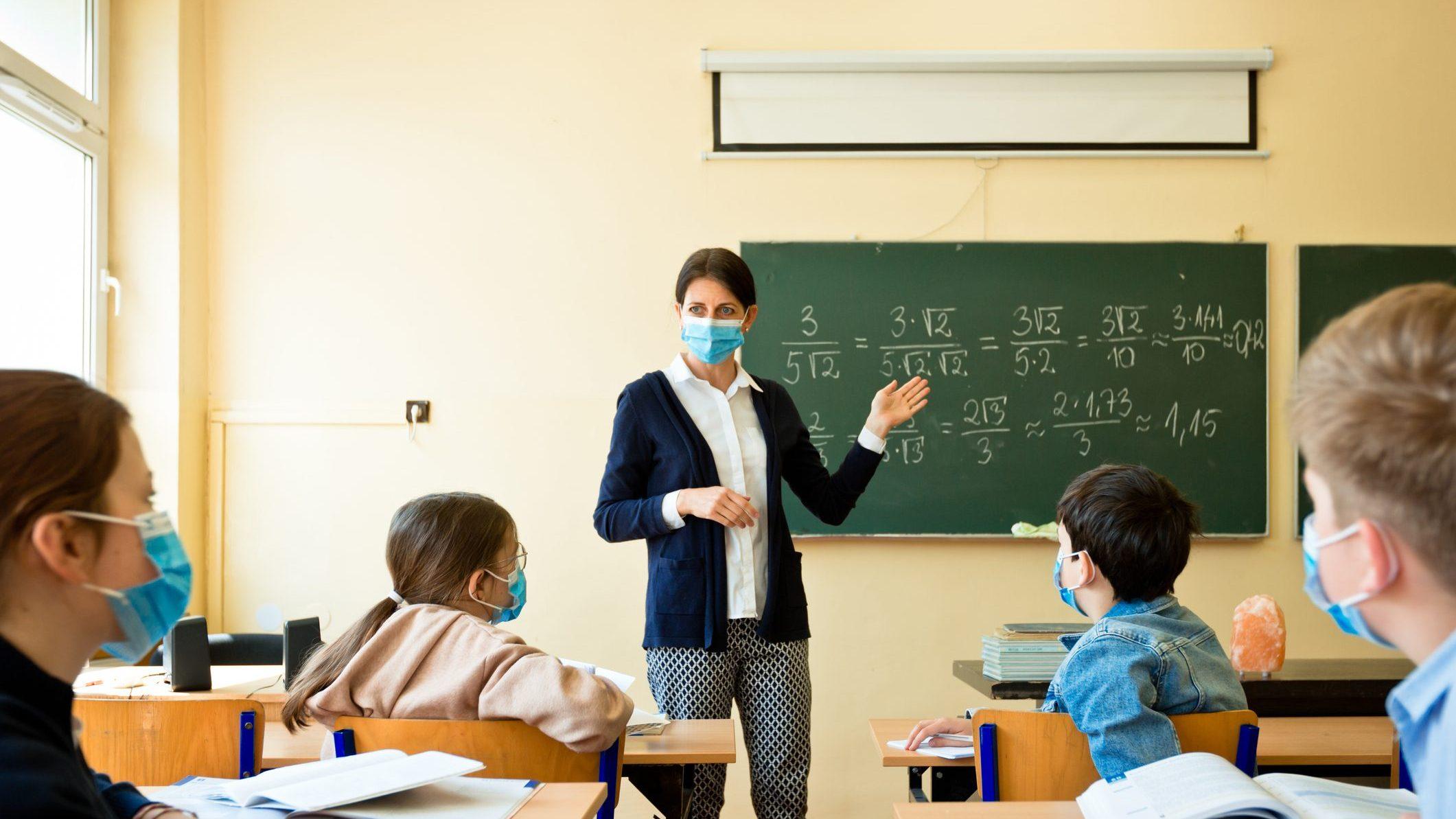 foto di una classe con dei bambini e un'insegnante a scuola che indossano le mascherine contro il coronavirus