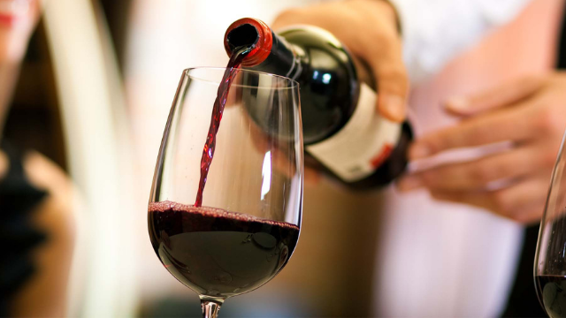 foto di una persona che versa del vino rosso in un bicchiere